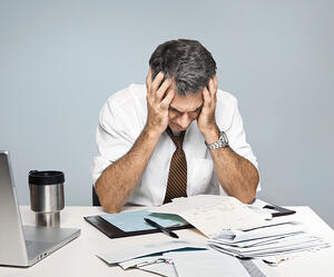 Stressed man with paperwork