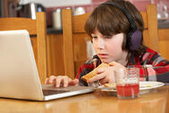 Young boy on laptop in kitchen